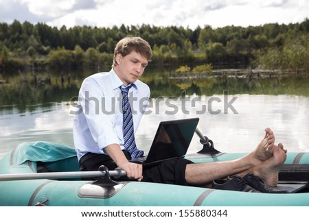 Dressed man in boat and reading from laptop