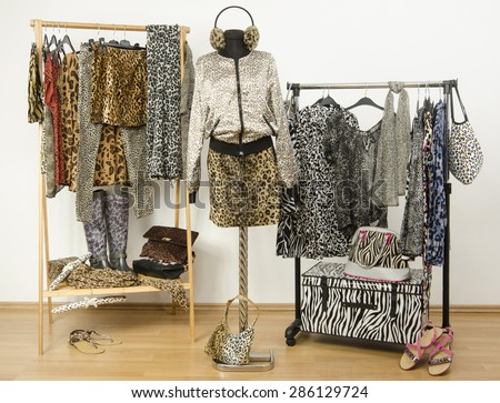 Dressing closet with animal print clothes arranged on hangers. Cheetah print fall outfit on a mannequin. Colorful wardrobe with jungle pattern clothes and accessories. - stock photo