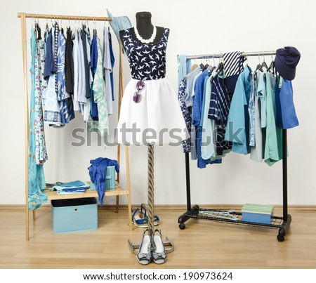 Dressing closet with blue clothes arranged on hangers. Cute summer outfit on a mannequin.  Wardrobe full of all shades of blue clothes, shoes and accessories.  - stock photo