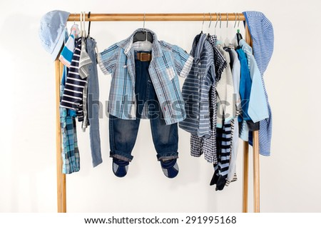 Dressing closet with clothes arranged on hangers.Blue and white wardrobe of newborn,kids, toddlers, babies full of all clothes.Many t-shirts,pants, shirts,blouses,blue hat, onesie hanging - stock photo