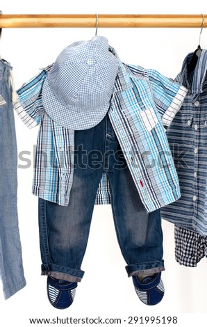 Dressing closet with clothes arranged on hangers.Blue and white wardrobe of newborn,kids, toddlers, babies full of all clothes.T-shirts,pants, shirts,blue hat hanging - stock photo