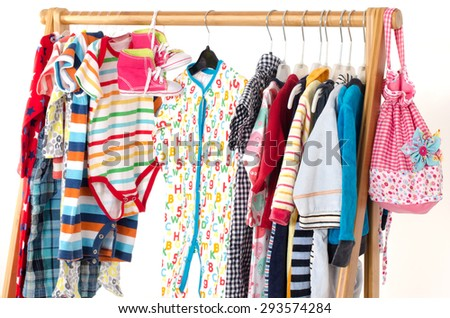 Dressing closet with clothes arranged on hangers.Colorful wardrobe of newborn,kids, toddlers, babies on a rack.Many t-shirts,pants, shirts,blouses, onesie hanging - stock photo