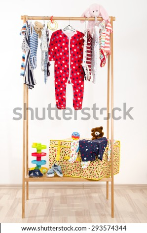 Dressing closet with clothes arranged on hangers.Colorful wardrobe of newborn,kids, toddlers, babies full of all clothes.Many t-shirts,pants, shirts,blouses, onesie hanging, rabbit and bear toy - stock photo