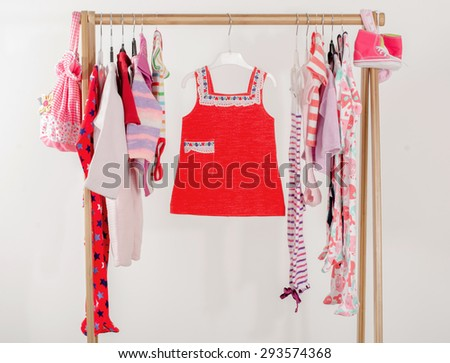 Dressing closet with clothes arranged on hangers.Red wardrobe of newborn,kids, toddlers, babies on a rack.Many t-shirts,pants, shirts,blouses, onesie hanging, little girl red dress - stock photo