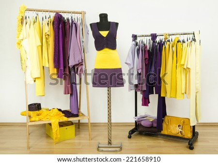 Dressing closet with complementary colors violet and yellow clothes.Wardrobe with purple and yellow clothes arranged on hangers and an outfit on a mannequin. - stock photo