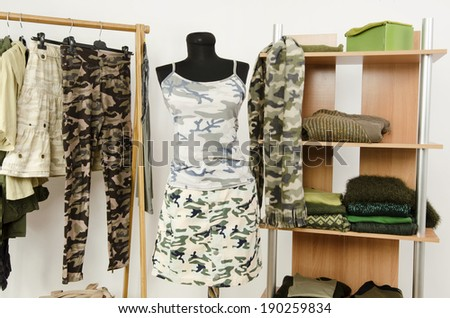 Dressing closet with military camouflage khaki green clothes arranged on hangers and shelf, outfit on a mannequin. Wardrobe with camo pattern clothes and accessories. - stock photo