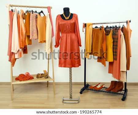 Dressing closet with orange clothes arranged on hangers and a dress on a mannequin. Wardrobe full of all shades of orange clothes, shoes and accessories. - stock photo