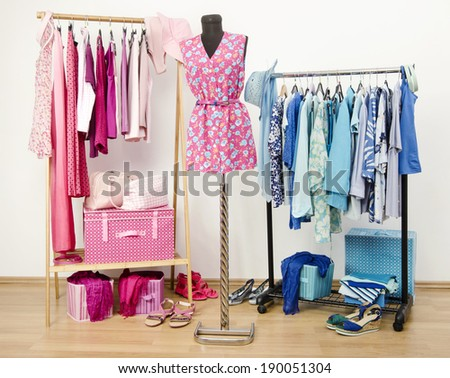 Dressing closet with pink and blue clothes arranged on hangers and an outfit on a mannequin. Wardrobe full of all shades of blue and pink clothes, shoes and accessories. - stock photo