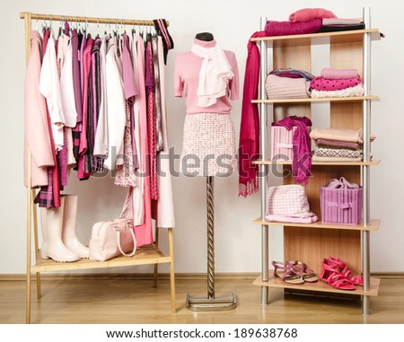 Dressing closet with pink clothes arranged on hangers and shelf, outfit on a mannequin. Wardrobe full of all shades of pink clothes, shoes and accessories. - stock photo