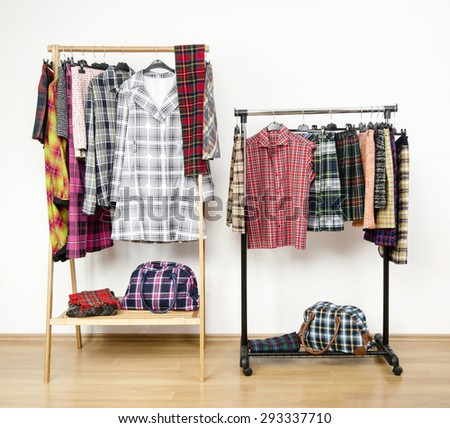 Dressing closet with plaid clothes arranged on hangers on racks.  Colorful wardrobe with tartan clothes and accessories. - stock photo