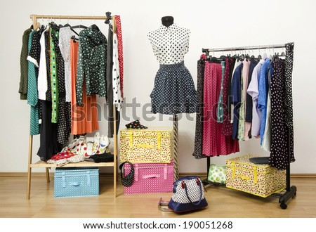 Dressing closet with polka dots clothes arranged on hangers and an outfit on a mannequin. Colorful wardrobe with polka dots clothes and accessories. - stock photo