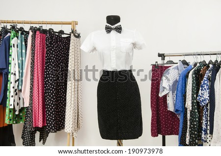 Dressing closet with polka dots clothes arranged on hangers. White shirt with bowtie and a black skirt on a mannequin. Colorful wardrobe with clothes and accessories. Girl masculine look. - stock photo