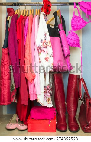 Dressing closet with red and pink clothes arranged on hangers - stock photo