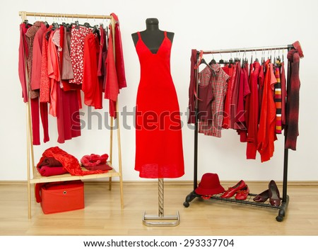 Dressing closet with red clothes arranged on hangers and a dress on a mannequin.  Wardrobe full of all shades of red clothes, shoes and accessories. - stock photo