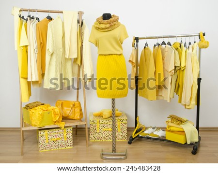 Dressing closet with yellow clothes arranged on hangers and a winter outfit on a mannequin. Wardrobe full of all shades of yellow clothes, shoes and accessories. - stock photo