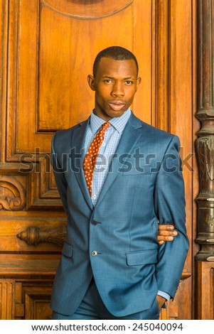 Dressing formally in blue suit, patterned shirt and necktie, short haircut, a arm crossing back, a hand in pocket, a young guy is standing in the front of an old style office door, looking at you. - stock photo