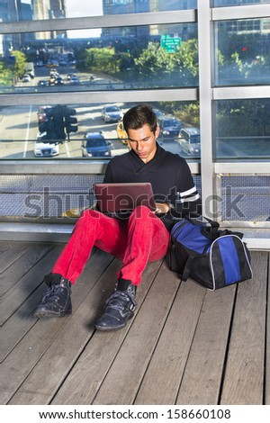 Dressing in a black shawl collar sweater and red jeans, carrying a blue bag, a young guy is sitting on the floor by a big glass wall, working on a computer. The background is a busy street scene.  - stock photo