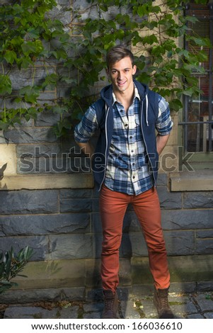 Dressing in a blue and white pattern shirt,  a blue hoody vest,  red jeans, a young guy is standing by a window with green ivy leaves. / Portrait of Young Guy - stock photo