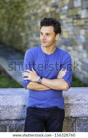 Dressing in a blue long sleeves with roll-tab Henley shirt, wearing a wristwatch, crossing arms,  a young handsome guy is relaxing outside. / Relaxing Outside - stock photo