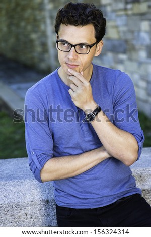 Dressing in a blue long sleeves with roll-tab Henley shirt, wearing glasses and a wristwatch, crossing arms and one hand touching his chin, a young handsome guy is thinking outside. / Thinking Outside - stock photo