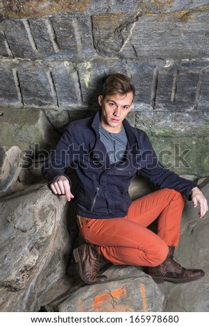 Dressing in a blue slim fit jacket,  red jeans and brown leather boot shoes, a young guy is squatting among rocks, thoughtfully looking at you. / On Rocks - stock photo
