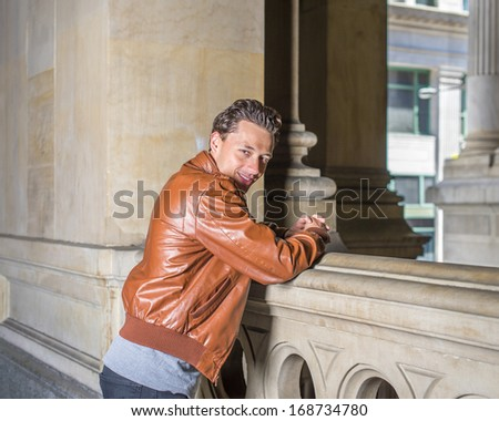 Dressing in a brown leather jacket, gray undershirt, black pants,  a young handsome guy is standing by a fence on the balcony, his head turning around, smiling and looking at you. / waiting for you