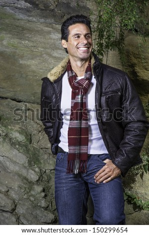 Dressing in a dark brown leather jacket, a long pattern scarf and white sweater, a handsome middle age guy is waiting for you. / Waiting for you - stock photo