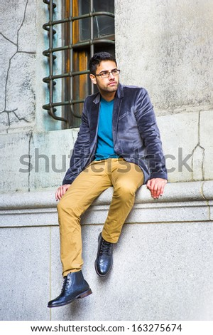 Dressing in a dark purple woolen blazer, blue sweater, dark yellow pants and leather boot shoes, wearing glasses, a young guy with bread and mustache is sitting by an old style window, relaxing.