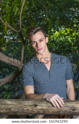 Dressing in a gray long sleeves with roll-tab Henley shirt, a young handsome guy is standing in a wood area and thoughtfully looking at you. / Portrait of Young Handsome Guy - stock photo