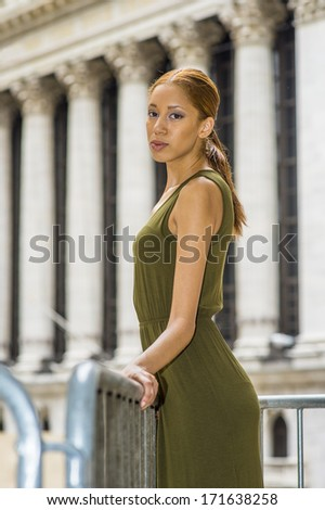Dressing in a green Tank Dress,  a young black girl is standing in the front of office buildings to take a break. / Relaxing Outside