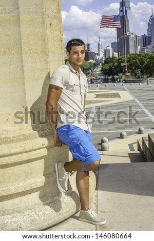 Dressing in a iron short sleeve shirt, blue shorts, a young attractive guy is standing by a column and looking at you. /Traveler - stock photo