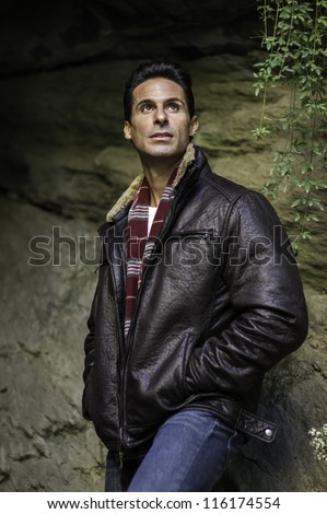Dressing in a leather jacket, a long scarf, a handsome mid-age guy is hopefully looking up./Looking Up - stock photo
