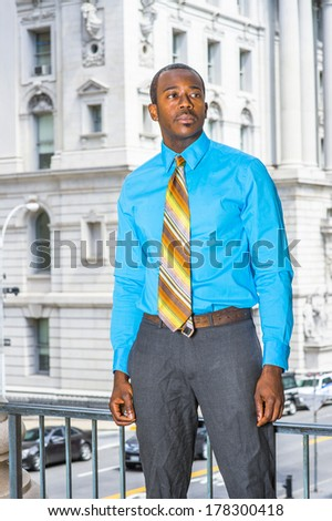 Dressing in a light blue shirt, gray pants,  a colorful pattern tie, a young black businessman is standing outside an office building, looking forward. / Portrait of Young Businessman