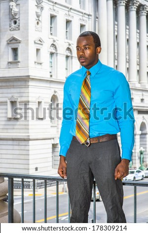 Dressing in a light blue shirt, gray pants,  a colorful pattern tie, a young black businessman is standing outside an office building, lost in thought. / Thinking Outside