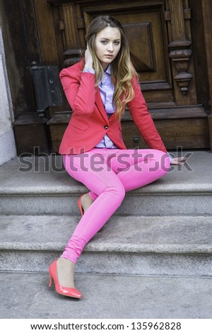Dressing in a pink blazer, pink pants and pink shoes, a young teenage girl is sitting on door steps and relaxing./Dressing in Pink - stock photo