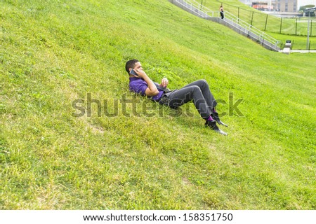 Dressing in a purple shirt, gray pants and a black tie, a young handsome businessman is lying on grasses and talking on the phone. / Taking a Break - stock photo