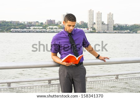 Dressing in a purple shirt, gray pants and a black tie, a young handsome college student with a little beard and mustache is standing by a river, seriouslly reading a red book. / Reading Outside