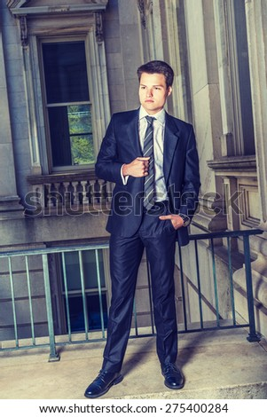 Dressing in black suit, necktie, white shirt, leather shoes, a young college student standing by railing in vintage style office building on campus, looking forward. Instagram filtered effect.