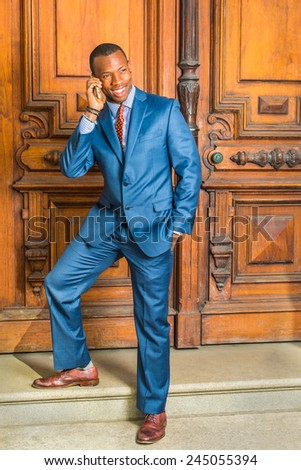 Dressing in blue suit, patterned shirt, necktie, short haircut, a young black businessman is standing by old style office door, feet stepping on stairs, tilting head, smiling, making a phone call. - stock photo