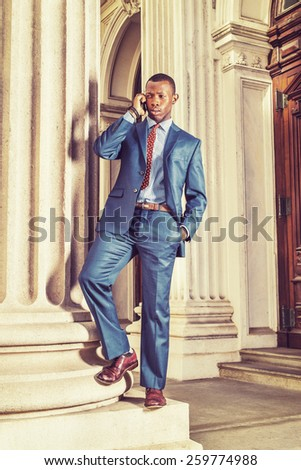Dressing in blue suit, tie, leather shoes, ear stub, , a young black businessman standing outside vintage style office building, frown, unhappy, calling on his mobile phone. Instagram filtered look. - stock photo