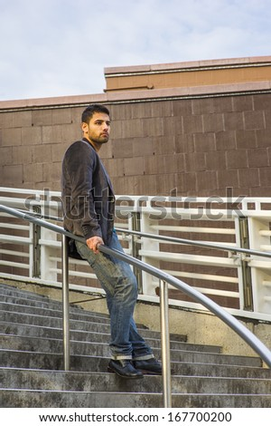 Dressing in dark purple woolen blazer, jeans and leather shoes, a young guy with beard and mustache is standing against a metal railing on stairs, under sunshine of sunset, thinking. /Thinking Outside