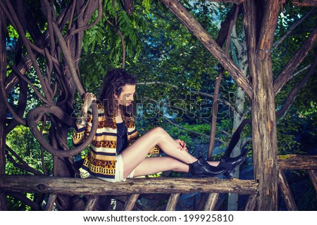 Dressing in patterned fashion jacket, shorts, bracelet, boot shoes, a teenager girl with curly long hair is sitting on fence, hand holding a rattan, looking down at her bare legs, relaxing, thinking.  - stock photo