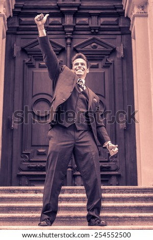 Dressing in three pieces suit, necktie, a handsome, sexy, middle age businessman standing on stairs in the front of office, raising his arm, thumbs up, smiling, celebrating his victory. - stock photo