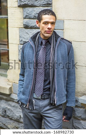 Dressing in woolen jacket with shoulder pads, tie, long scarf and gloves, a young handsome guy is standing against the wall, charmingly looking at you / Waiting for You - stock photo