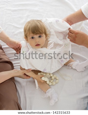 Dressing up a child on white bed.Hands of mother and father.