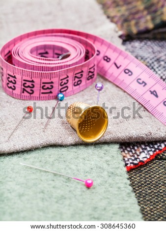 dressmaking still life - pink measuring tape, pins, thimble on tissue - stock photo