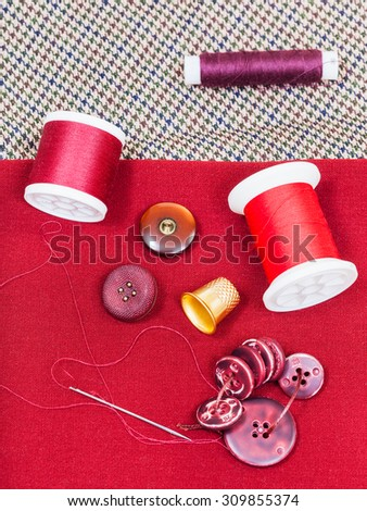 dressmaking still life - top view of bobbins with sewing thread, buttons, thimble, needle on red cloth - stock photo