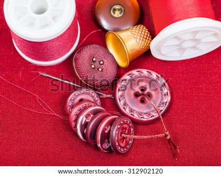 dressmaking still life - top view of bobbins with sewing thread, buttons, thimble, needle on red textile - stock photo