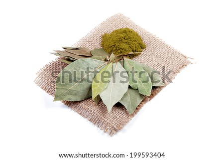 Dried and ground bay leaves on a linen napkin - stock photo