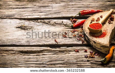Dried and ground red chili pepper on oak stand. On wooden background. Free space for text . - stock photo